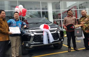 Director of Sales and Marketing Division PT Mitsubishi Motors Krama Yudha Sales Indonesia, Osamu Iwaba (dua kiri) berfose bersama konsumen pertama PT Nusantara Berlian Motor, Rabu (30/08/2017). (akses.co/din)